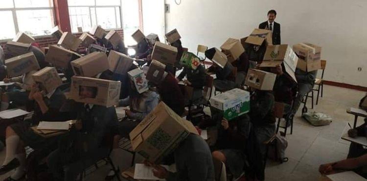 На фото мексиканский учитель вместе со студентами в картонных коробках на экзамене